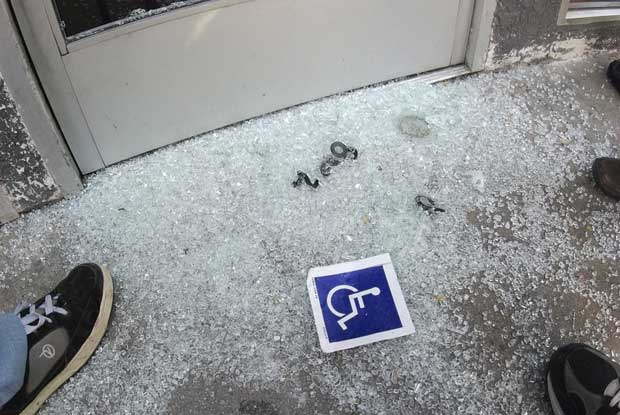 Broken glass and a handicap sign on the sidewalk