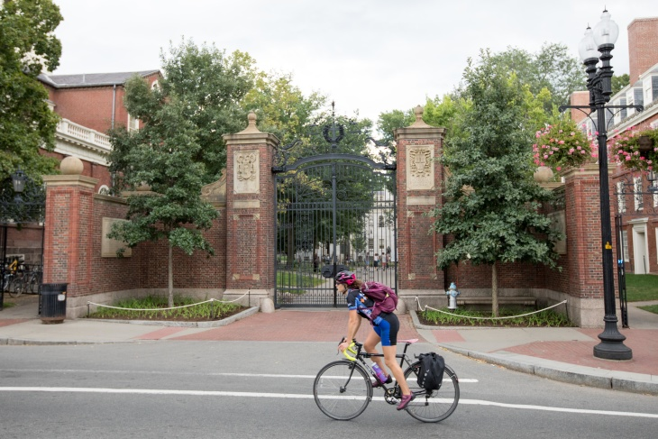 A bicyclist rides past a gate to Harvard University on Aug. 30 2018 in Cambridge Massachusetts