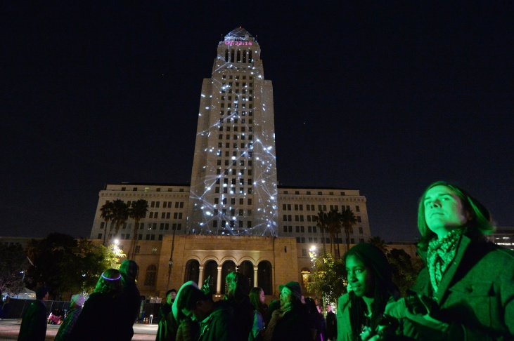 file city hall is lit by two dimensional projected images while people watch a band perform as they celebrate the new year at the grand parks nyela